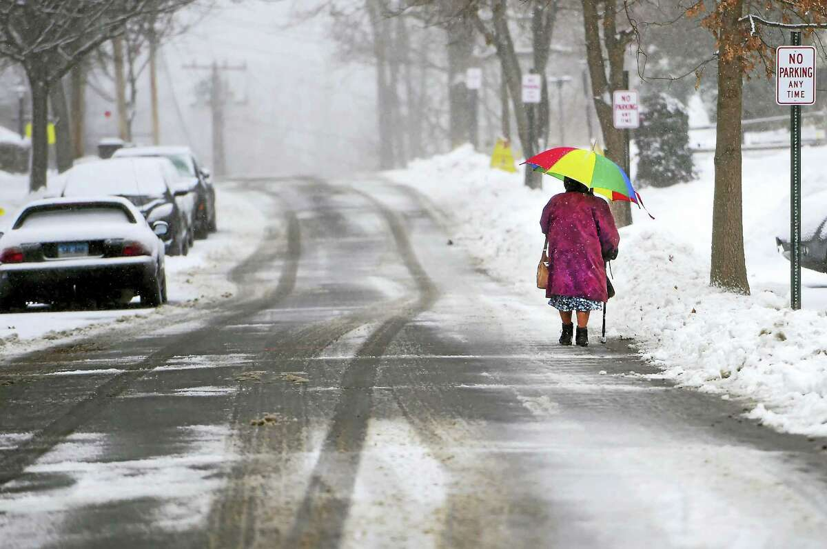 A woman walks in the snowfall down Bradley Avenue in Branford Monday. Schools in Branford were set to open 90 minutes late Tuesday as the town cleaned up from the latest storm.