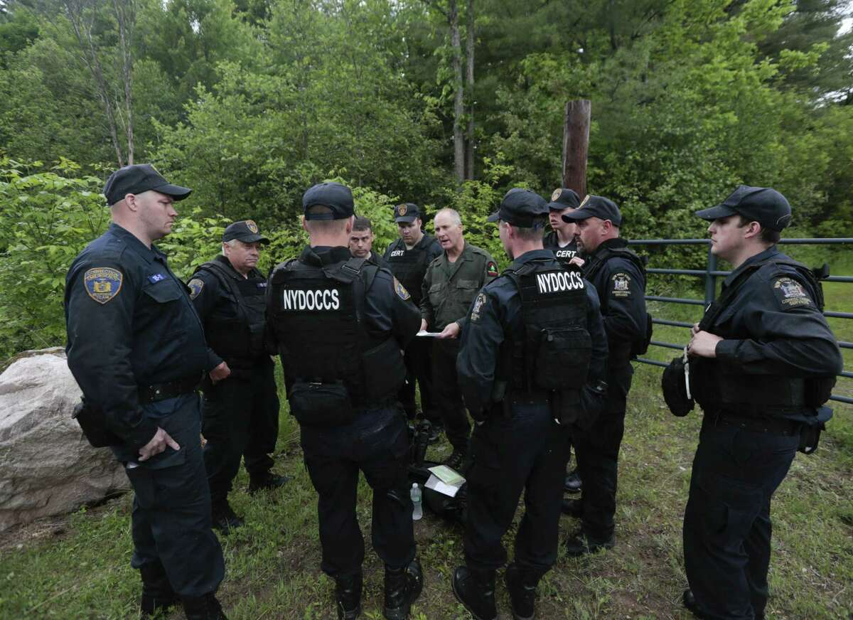 State forest ranger Dan Fox reviews a map with members of the New York State Department of Corrections and Community Supervision emergency response team before entering a wooded area in search of two prisoners who escaped from the Clinton Correctional Facility on Monday, June 8, 2015, in Dannemora, N.Y. The two murderers who escaped from the prison by cutting through steel walls and pipes remain on the loose Monday as authorities investigate how the inmates obtained the power tools used in the breakout.
