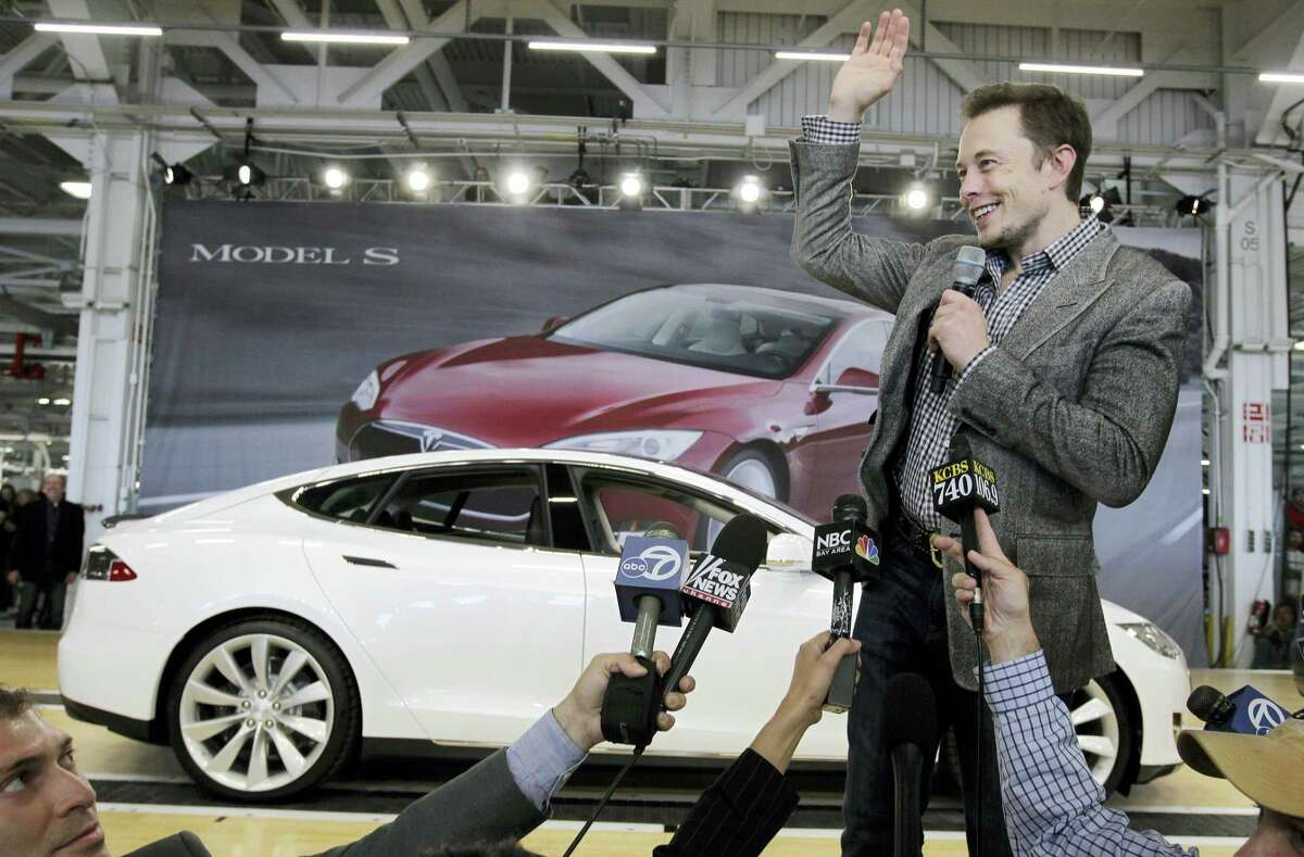 In this June 22, 2012 photo, Tesla CEO Elon Musk waves during a rally at the Tesla factory in Fremont, Calif.
