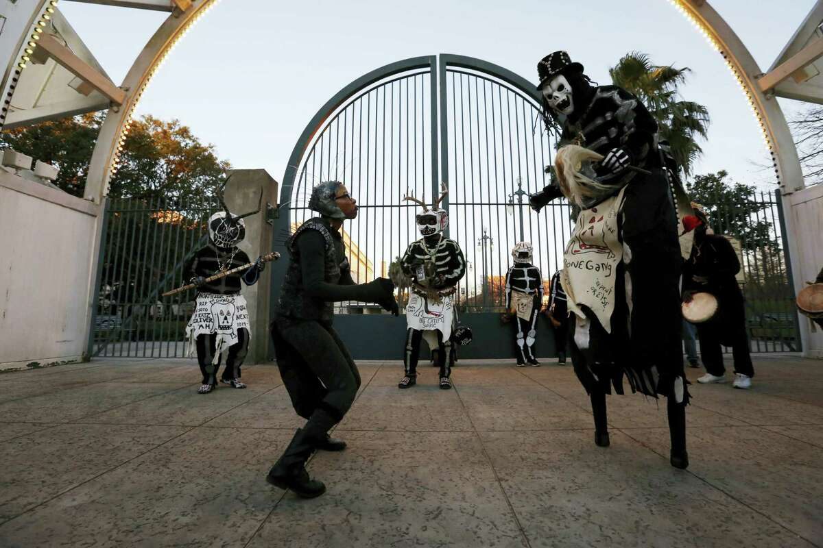 Members of the North Side Skull & Bone Gang dance in front of the Louis Armstrong park during the wake up call for Mardi Gras, Tuesday, Feb. 9, 2016, in New Orleans. Their costumes are intended to represent the dead and they bring a serious message, reminding people of their mortality and the need to live a productive and good life.
