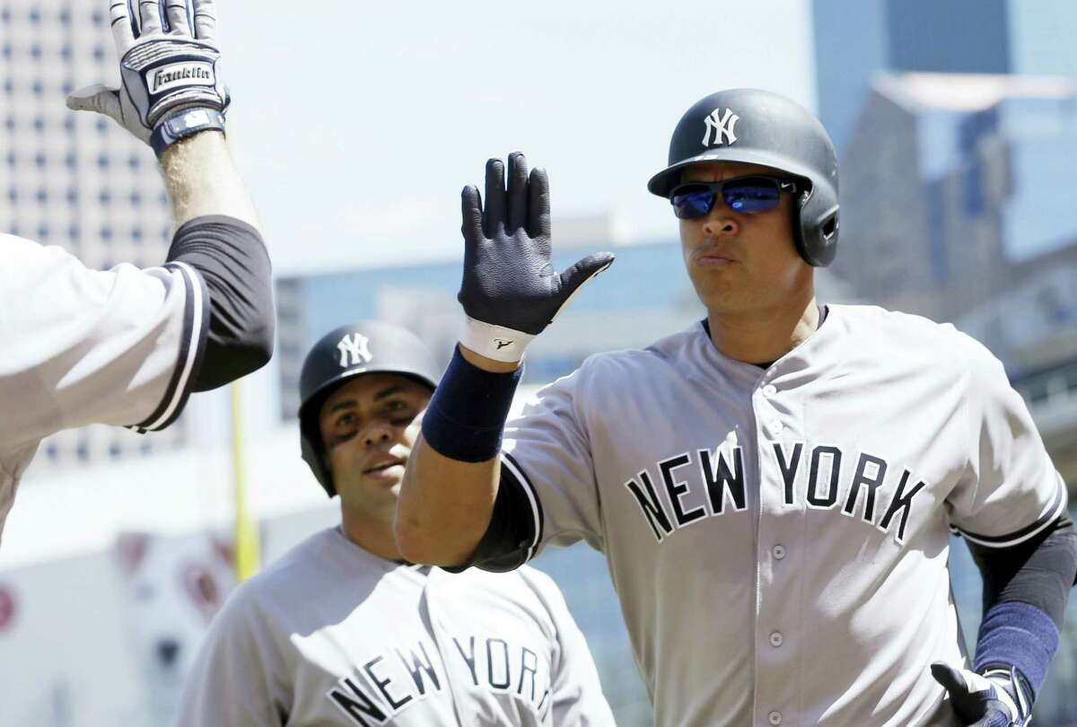 Alex Rodriguez, right, gets congratulations following his two-run home run in the seventh inning on Sunday.