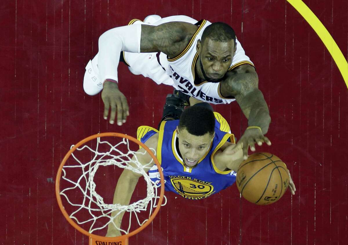 The Warriors' Stephen Curry, bottom, drives to the basket against the Cavaliers' LeBron James during Game 6 of the NBA Finals on Thursday. The two will face off in a rare Game 7 tonight in Oakland, Calif.