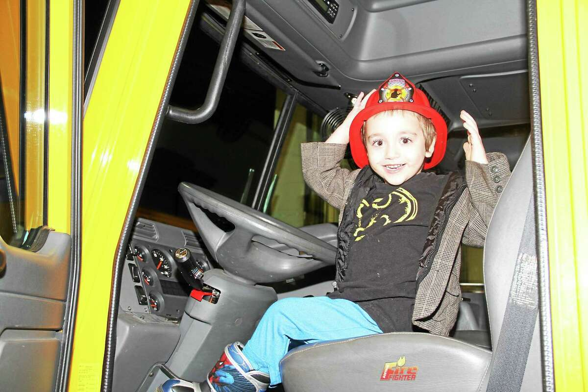 Dude Laboy, 3, of Torrington, gets to sit in the driver's seat of a fire engine Monday evening during an open house of the Torringford Volunteer Fire Department.