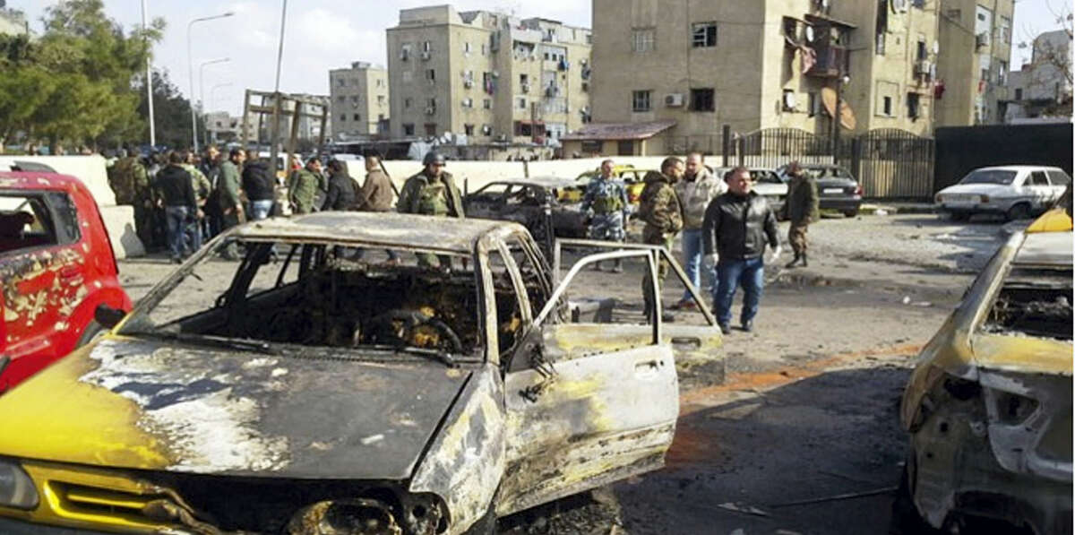 In this photo released by the Syrian official news agency SANA, soldiers and plainclothes policemen gather at the scene of an explosion that killed tens of people and wounded others in the Syrian capital of Damascus on Tuesday Feb. 9, 2016. The Islamic State group claimed responsibility for the suicide attack, that caused wide material damage to buildings and cars in the area. IS vowed to carry out more attacks in the future.