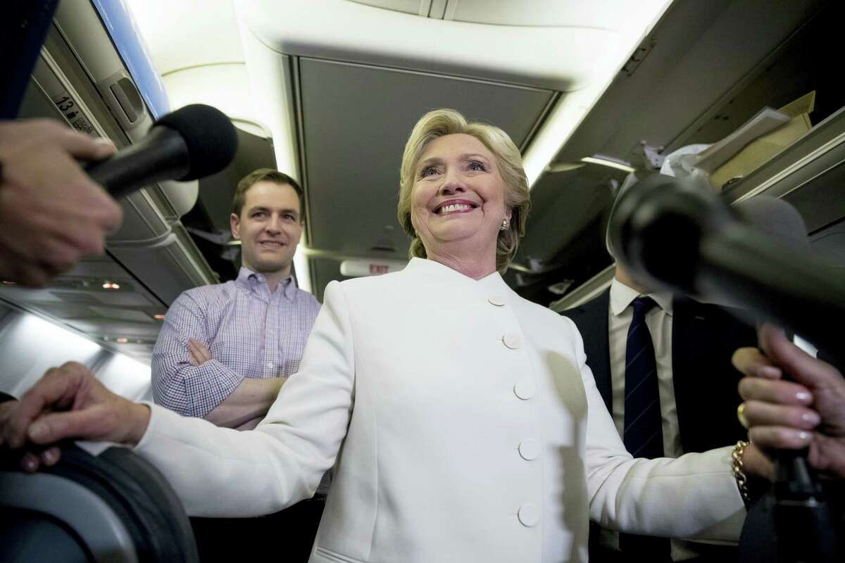 Democratic presidential candidate Hillary Clinton, center, accompanied by Campaign Manager Robby Mook, left, and traveling press secretary Nick Merrill, right, smiles as she speaks with members of the media aboard her campaign plane at McCarran International Airport in Las Vegas on Oct. 19, 2016 following the third presidential debate.