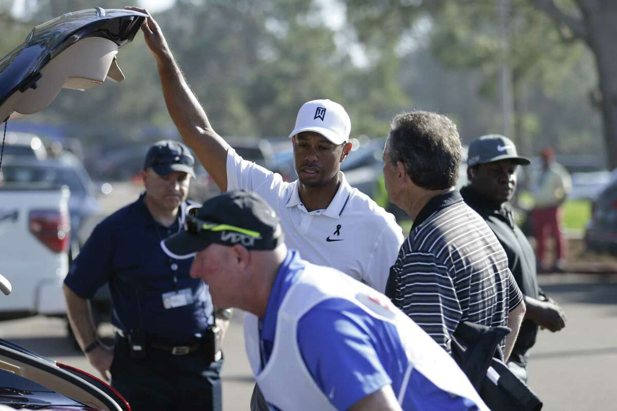 Tiger Woods loads his car after withdrawing in the first round of the Farmers Insurance Open Thursday in San Diego.