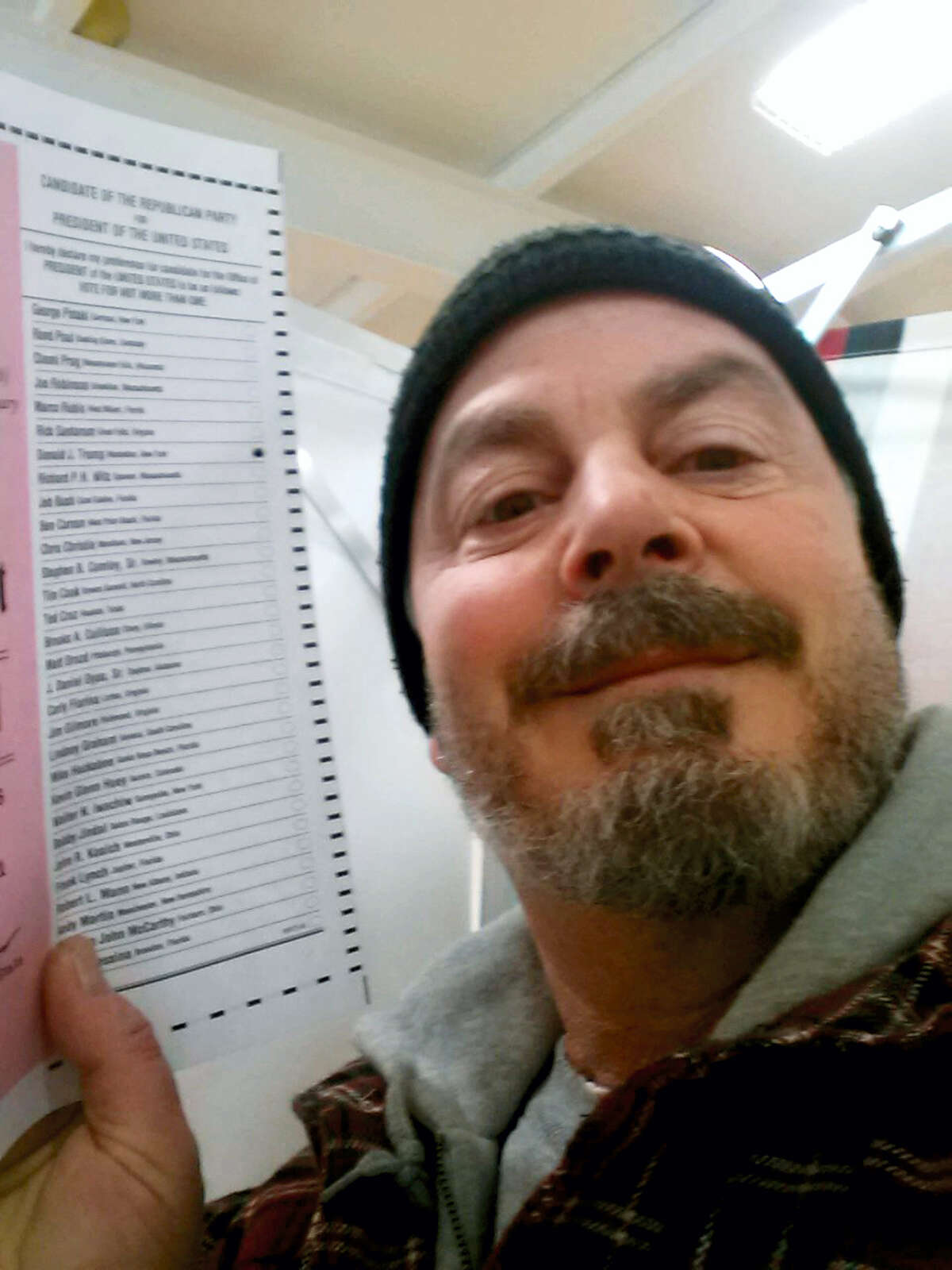 In this Feb. 9, 2016 photo, provided by Bill Phillips, of Nashua, N.H., Phillips takes a selfie with his marked election ballot. The secrecy of the voting booth may soon be a thing of the past. Ballot selfies, where people use smartphones to photograph and share their marked ballots online, are becoming more common, as voters young and old look to share their views with family, friends and the world. But what they don't realize is they may be breaking the law, depending on where they live.
