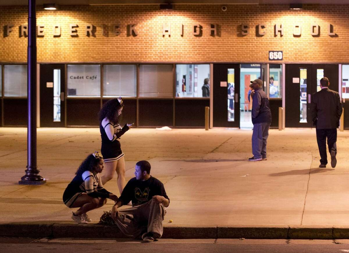 People gather outside the entrance to Frederick High School following a shooting in Frederick, Md., Wednesday, Feb. 4, 2015. Police and school officials said students were shot outside the school while a basketball game was being played inside. (AP Photo/The Frederick News-Post, Bill Green)