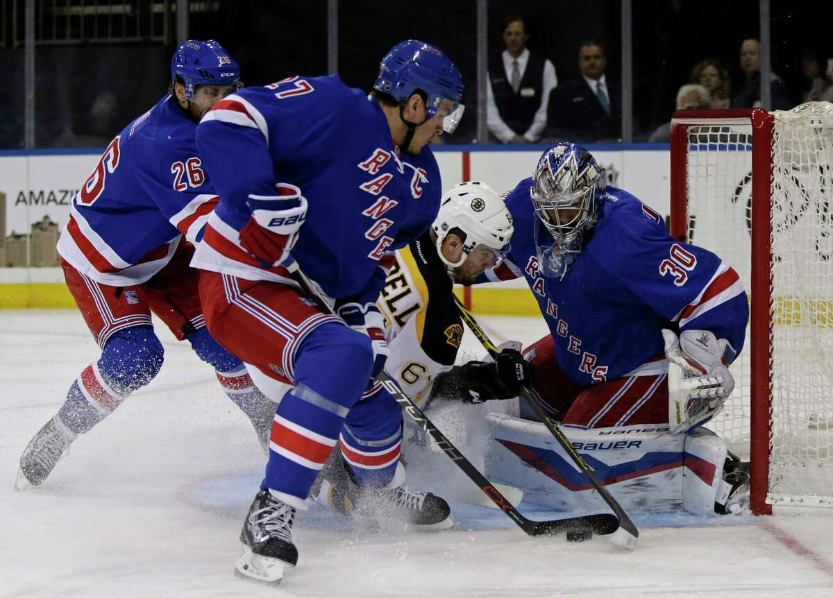 New York Rangers goalie Henrik Lundqvist (30) makes a save on a shot by Boston Bruins right wing Tyler Randell (64) as Rangers defenseman Ryan McDonagh (27) looks on during the first period of an NHL preseason hockey game at Madison Square Garden in New York, Wednesday, Sept. 30, 2015. (AP Photo/Adam Hunger)
