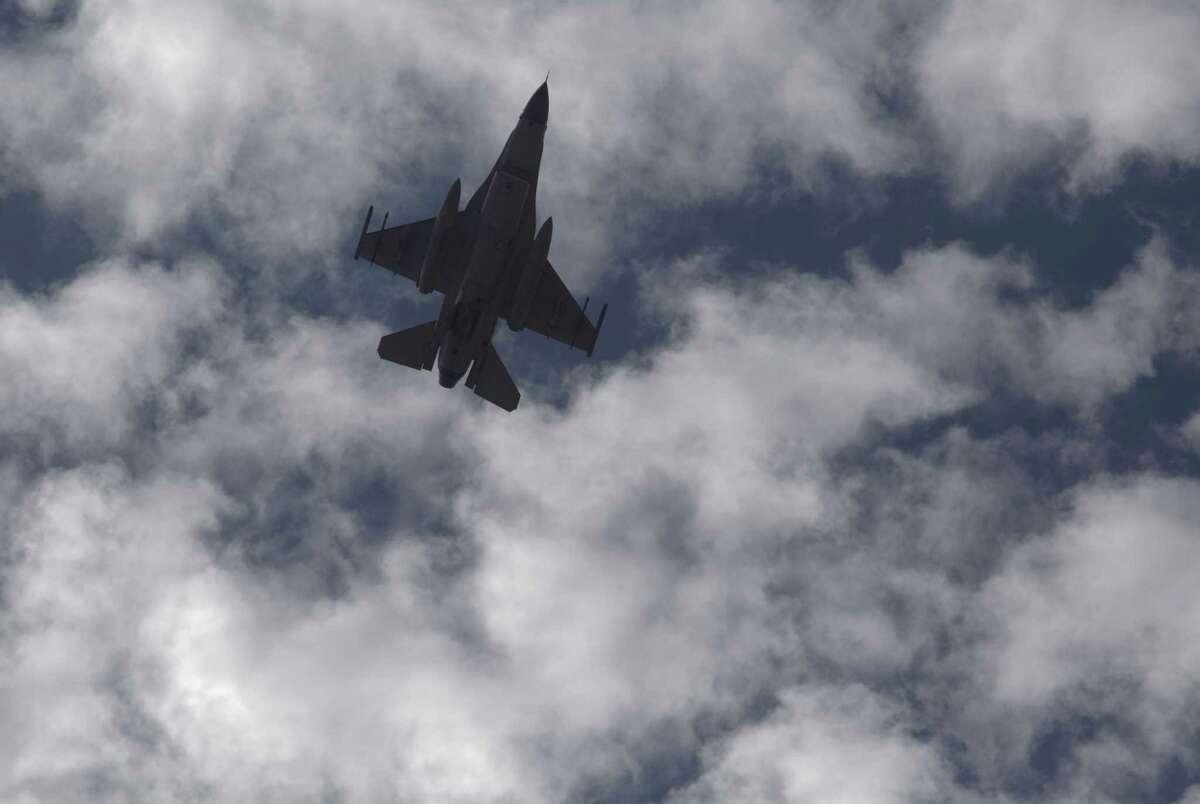 A Jordanian Air Force fighter jet flies over the village of Ai as Jordanian King Abdullah II visits to offer his condolences to the tribe of the slain Jordanian pilot, Lt. Muath al-Kaseasbeh at their home village near Karak, Jordan, Thursday, Feb. 5, 2015. Jordan's king vowed to wage a