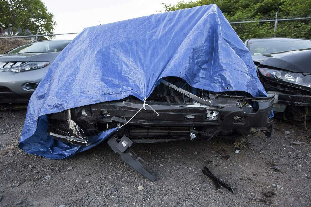 The damaged Mercedes-Maybach belonging to former New England Patriots linebacker Brandon Spikes is covered with a tarp in a tow yard in North Attleborough, Mass.