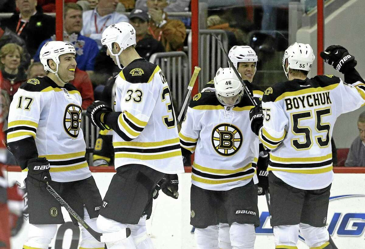 Boston Bruins' Milan Lucic (17), Zdeno Chara (33), of Slovakia, David Krejci (46), of the Czech Republic, and Johnny Boychuk (55) celebrate with Nathan Horton, rear, following Horton's goal against the Carolina Hurricanes during the second period of an NHL hockey game in Raleigh, N.C., Monday, Jan. 28, 2013. Boston won 5-3. (AP Photo/Gerry Broome)