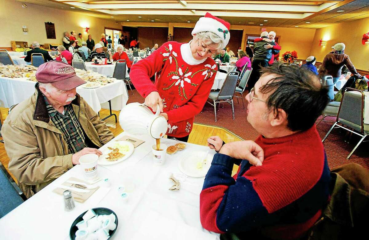 Connie Howe pours coffee for Ronald Read, left, and Dave Smith during the 2011 Charlie Slate Memorial Christmas breakfast at the American Legion in Brattleboro, Vt.