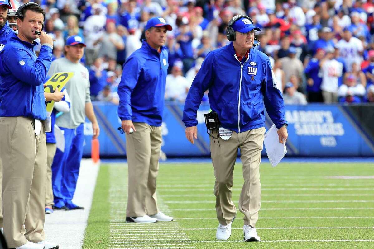 New York Giants head coach Tom Coughlin, right, walks on the field during Sunday's win over the Bills.