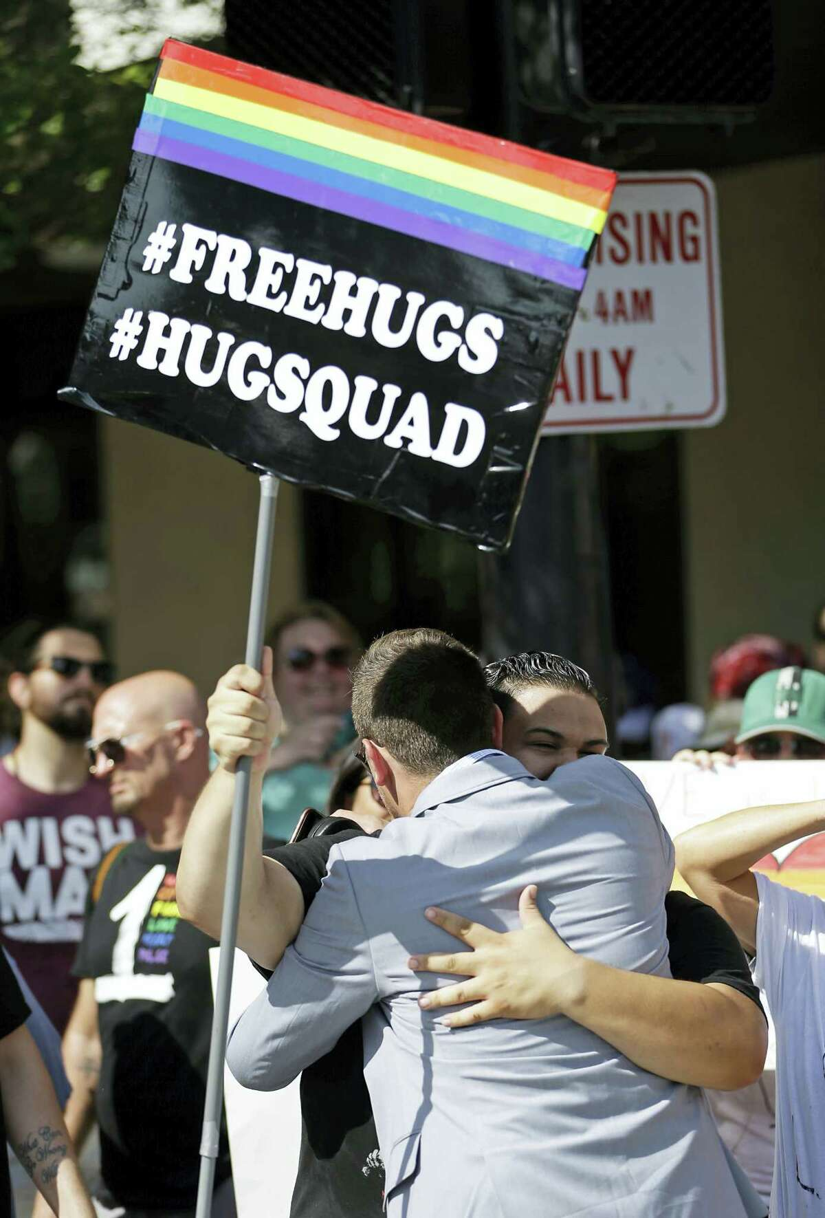 Counter demonstrators hug during a rally to show support and solidarity near the funeral service for Christopher Andrew Leinonen, one of the victims of the Pulse nightclub mass shooting, outside the Cathedral Church of St. Luke, Saturday, June 18, 2016, in Orlando, Fla.