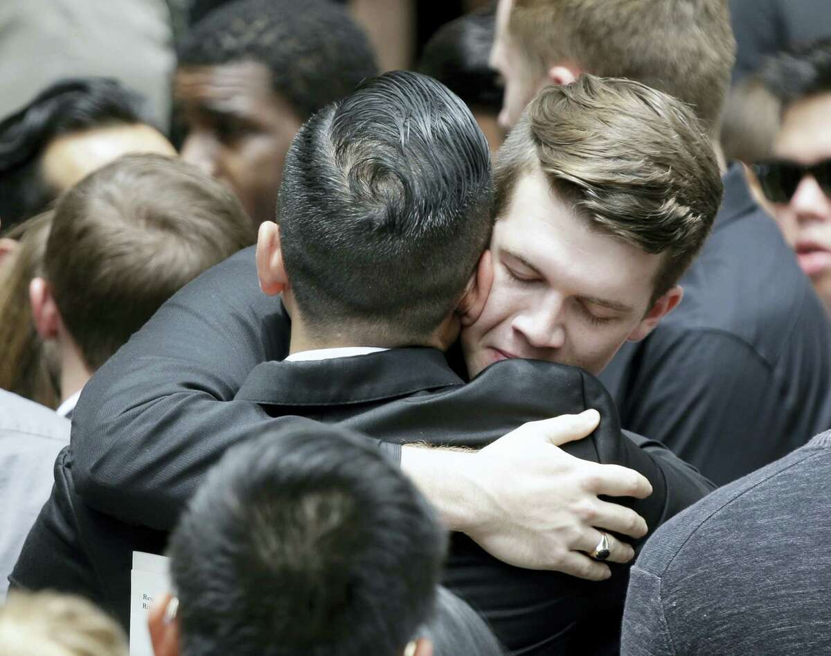 Mourners embrace following the funeral service for Christopher Andrew Leinonen, one of the victims of the Pulse nightclub mass shooting, outside the Cathedral Church of St. Luke, Saturday, June 18, 2016, in Orlando, Fla.
