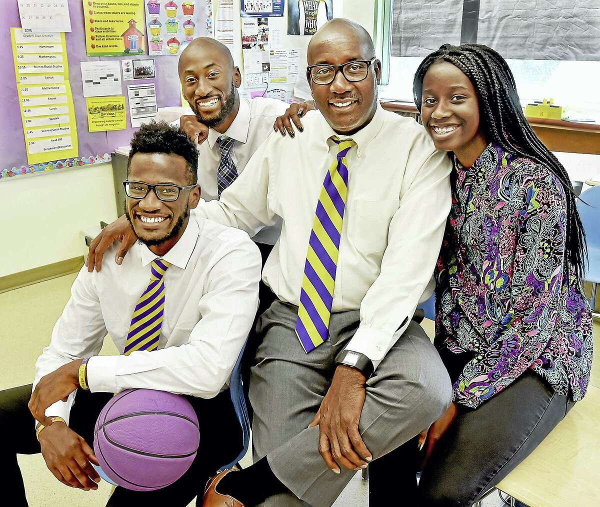 Larry Conaway, 62, the principal at New Light H.S and Riverside Educational Academy in New Haven with his son, Alexander, 23, a Trinsition Fellow and assistant basketball coach at Trinity College, Adham, 26, a teacher at the Davis St. School and Nyka, 15, a rising sophomore at Wilbur Cross, photographed in Adham's classroom, Tuesday, June 14, 2016.