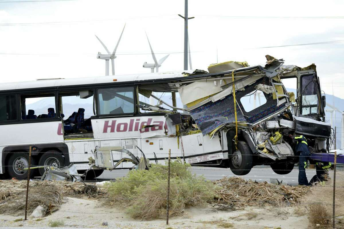 Workers prepare to haul away a tour bus that crashed with semi-truck on Interstate 10 just west of the Indian Canyon Drive off-ramp, in Desert Hot Springs, near Palm Springs, Calif., Sunday, Oct. 23, 2016. The tour bus and a semi-truck crashed on the highway in Southern California early Sunday, killing at least 11 people and injuring at least 30 others, some critically, the California Highway Patrol said.