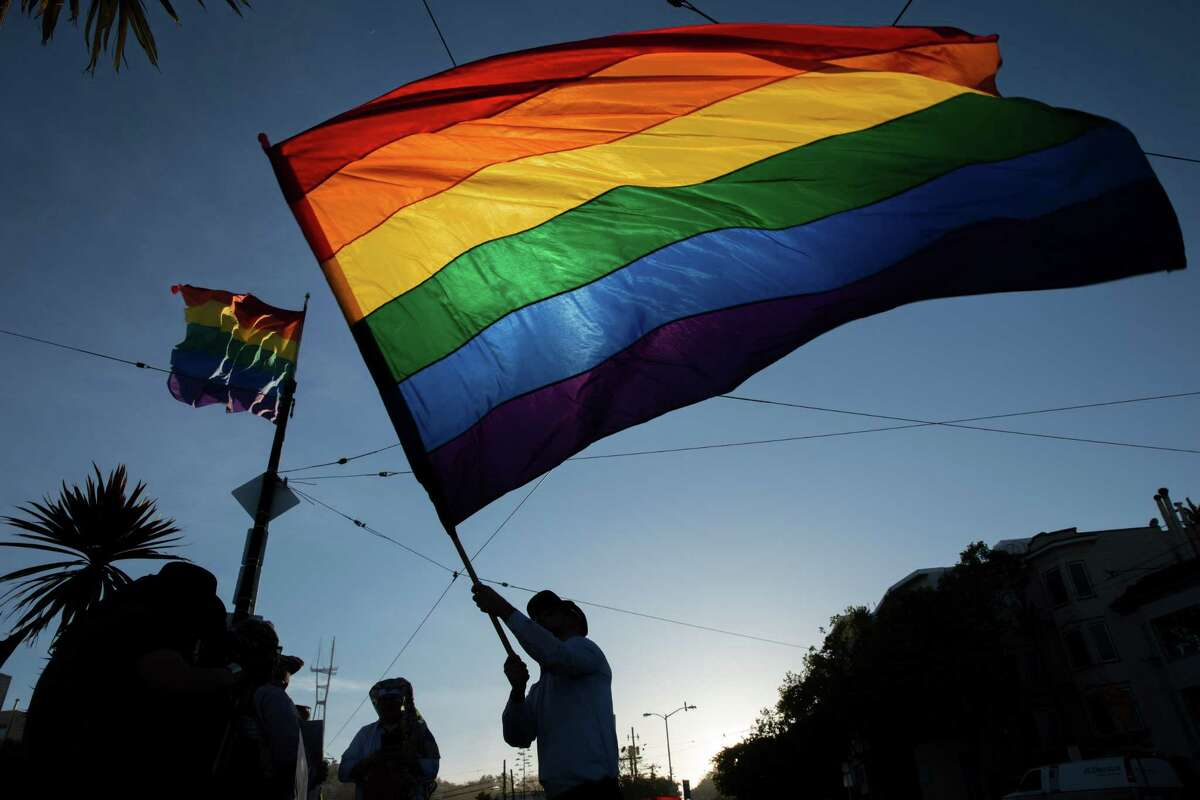 Tre Allen waves the rainbow flag in the Castro during a memorial for Gilbert Baker on Friday, March 31, 2017, in San Francisco, Calif. The memorial was for Baker, who designed the rainbow flag. Friends said Baker, age 65, died Thursday in his sleep at his home in New York. The rainbow flag has since become a symbol of the LGBT community recognized worldwide é?' celebrated at pride festivals, brandished at protests and raised every morning at the corner of Castro and Market streets.