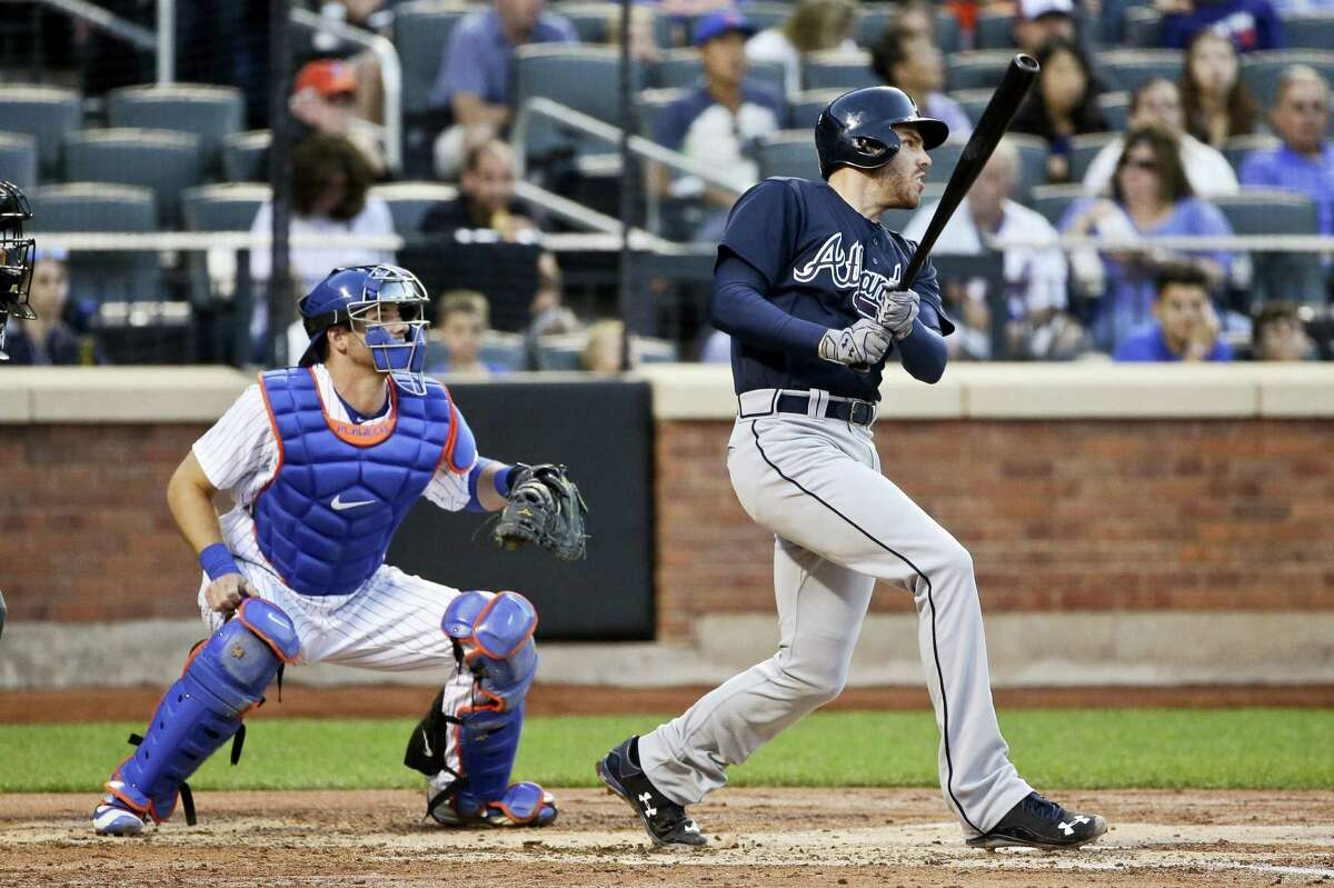 Mets catcher Kevin Plawecki and the Braves' Freddie Freeman watch Freeman's RBI double during the third inning on Friday.