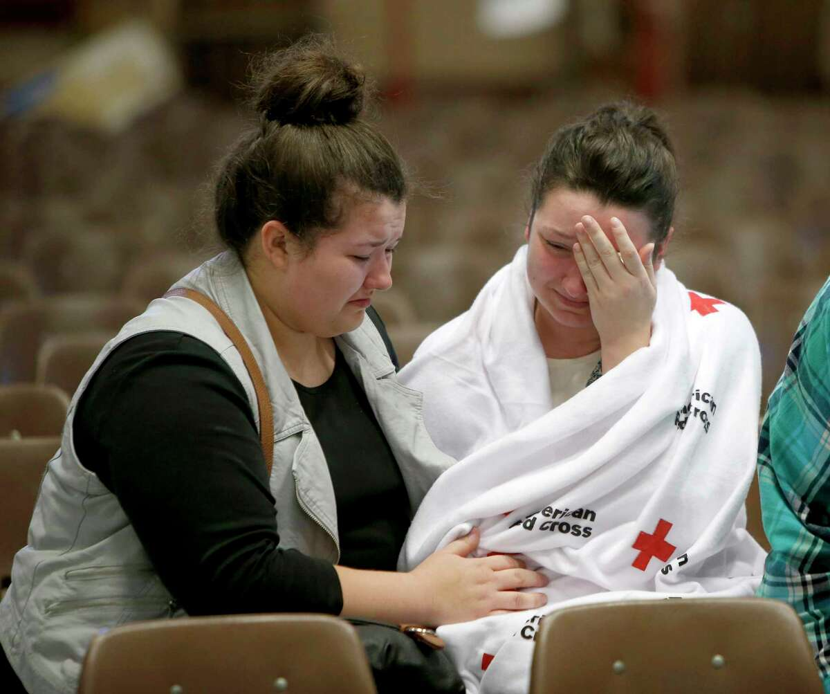 In this Oct. 1, 2015 photo, Hannah Miles, right, sits with her sister, Hailey, after a fatal shooting at Umpqua Community College in Roseburg, Ore. Harper-Mercer took multiple lives Thursday in chilling fashion before killing himself as officers closed in, placing the small town of Roseburg among settings that have become infamous for inexplicable violence.