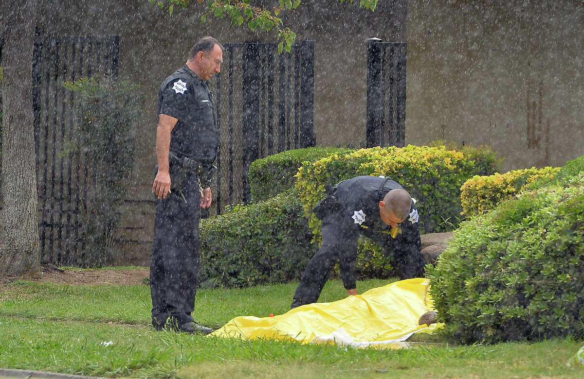 In this Oct. 1, 2015 photo, Fresno Police officers cover the body of a person after two were fatally shot at North San Pablo Avenue and East Barstow Avenue in Fresno, Calif.