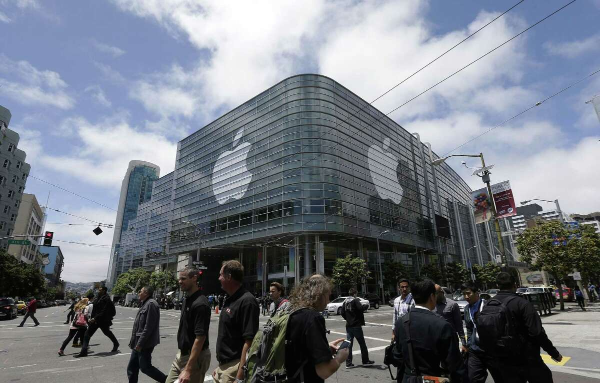 In this June 2, 2014 photo, pedestrians cross the street in front of the Moscone Center, which is hosting the Apple Worldwide Developers Conference, in San Francisco. Apple is expected to announce its new paid streaming-music service at its annual conference for software developers, which kicks off June 8, 2015.