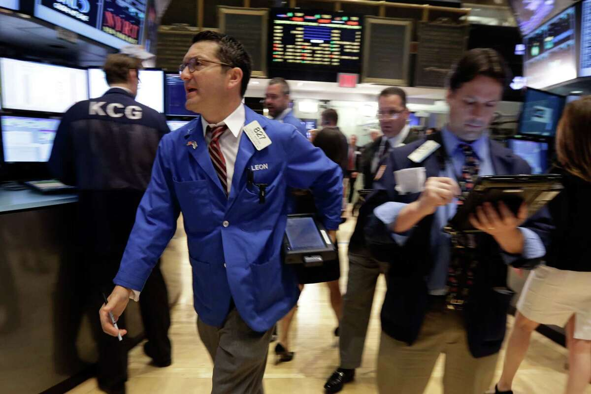 Leon Montana, left, works with fellow traders on the floor of the New York Stock Exchange Monday.