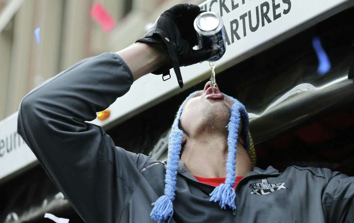 New England Patriots tight end Rob Gronkowski chugs a beer, tossed to him by a fan, during Wednesday's parade in Boston.