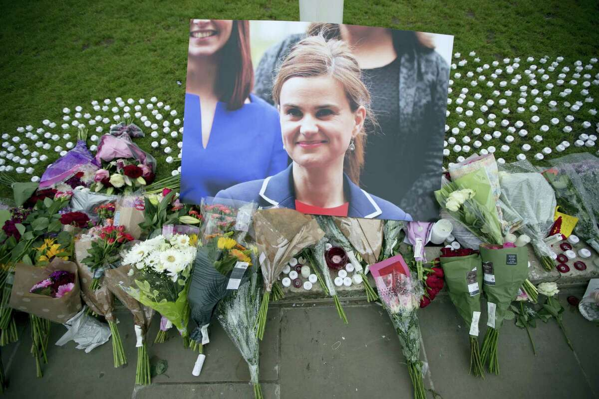 An image and floral tributes for Jo Cox, lay on Parliament Square, outside the House of Parliament in London, Friday, June 17, 2016, after the 41-year-old British Member of Parliament was fatally injured Thursday in northern England. The mother of two young children was shot to death Thursday afternoon in her constituency near Leeds. A 52-year-old man has been arrested but has not been charged. He has been named locally as Tommy Mair.