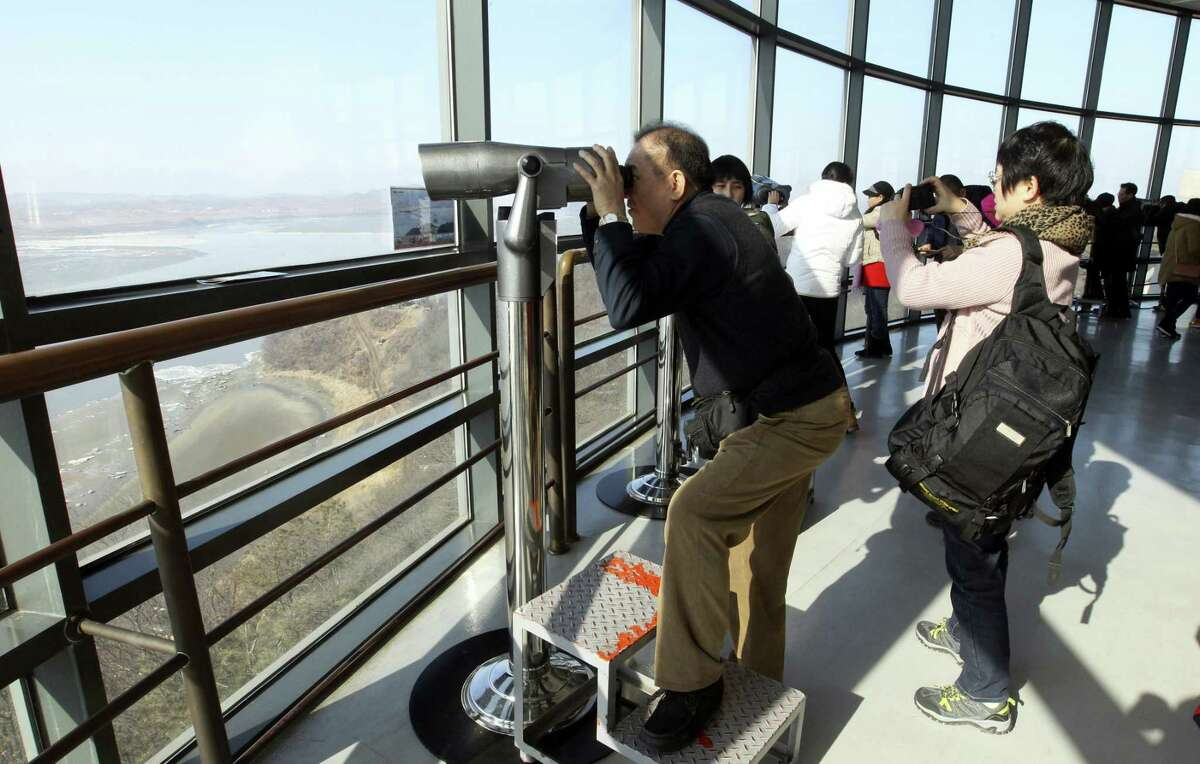 """Visitors watch the North Korean side at the unification observation post near the border village of Panmunjom, which has separated the two Koreas since the Korean War, in Paju, South Korea on Feb. 7, 2016. For North Korea's propaganda machine, the long-range rocket launch Sunday carved a glorious trail of """"fascinating vapor"""" through the clear blue sky. For South Korea's president, and other world leaders, it was a banned test of dangerous ballistic missile technology and yet another """"intolerable provocation."""""""