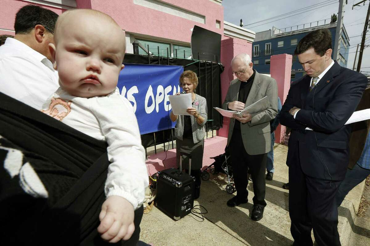 This photo taken March 5, 2014 shows seven-month old Abigail Dalton of Ridgeland, seeming to be listening as state Mississippi Sen. Chris McDaniel, R-Ellisville, right, prays with fellow abortion opponents, Laura Duran of Pro-Life Mississippi, left, and Rev. Mike O'Brien, pastor of St. Richard Catholic Church in Jackson, center, outside the Jackson Women's Health Organization clinic in Jackson, Miss., during the first day of a 40-day pro-life mobilization.