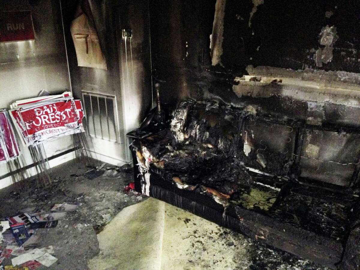 """A burned couch is shown next to warped campaign signs at the Orange County Republican Headquarters in Hillsborough, NC on Sunday, Oct. 16 2016. Someone threw flammable liquid inside a bottle through a window overnight and someone spray-painted an anti-GOP slogan referring to """"Nazi Republicans"""" on a nearby wall, authorities said Sunday. State GOP director Dallas Woodhouse said no one was injured."""