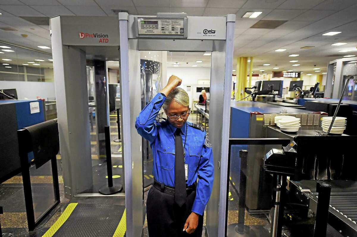 Barbara Toyer, a TSA supervisor, calibrates a walk-through metal detector for use at a security checkpoint at Ronald Reagan Washington National Airport on Dec. 22, 2014.