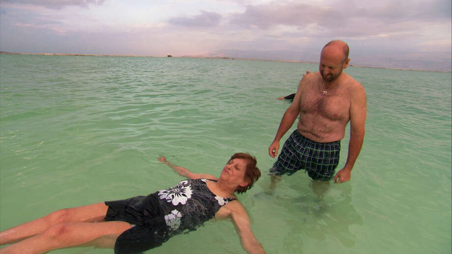 Helen Downs, a resident of the Jewish Home for the Elderly, floats in the Dead Sea as Andrew Banoff, the nursing home's director, monitors her swim during a 2011 trip to Israel. Photo: Contributed Photo / Fairfield Citizen contributed