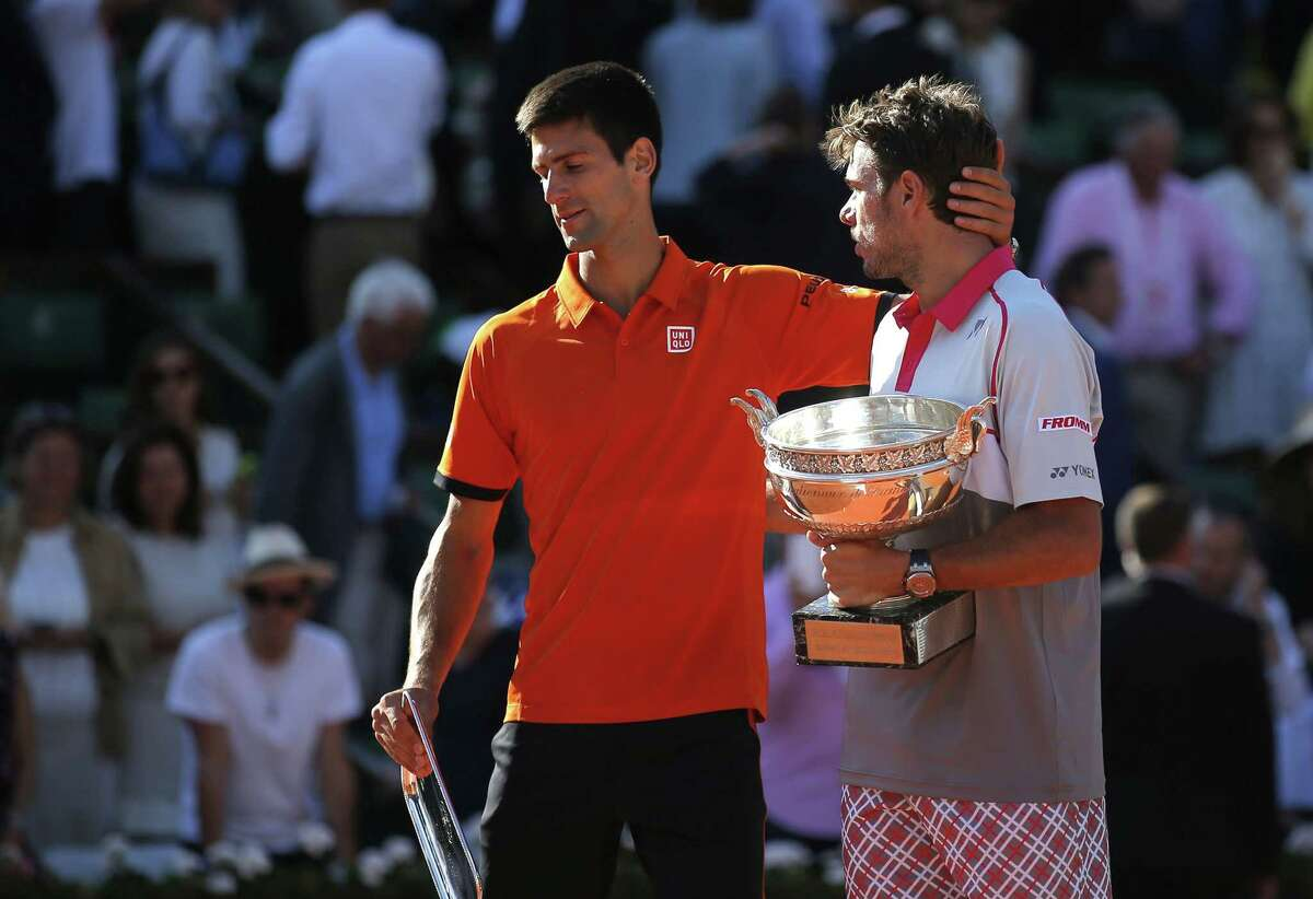 Switzerland's Stan Wawrinka, right, holds the cup while Serbia's Novak Djokovic leaves the ceremony after their men's final match at the Roland Garros stadium on Sunday. Wawrinka won 4-6, 6-4, 6-3, 6-4.
