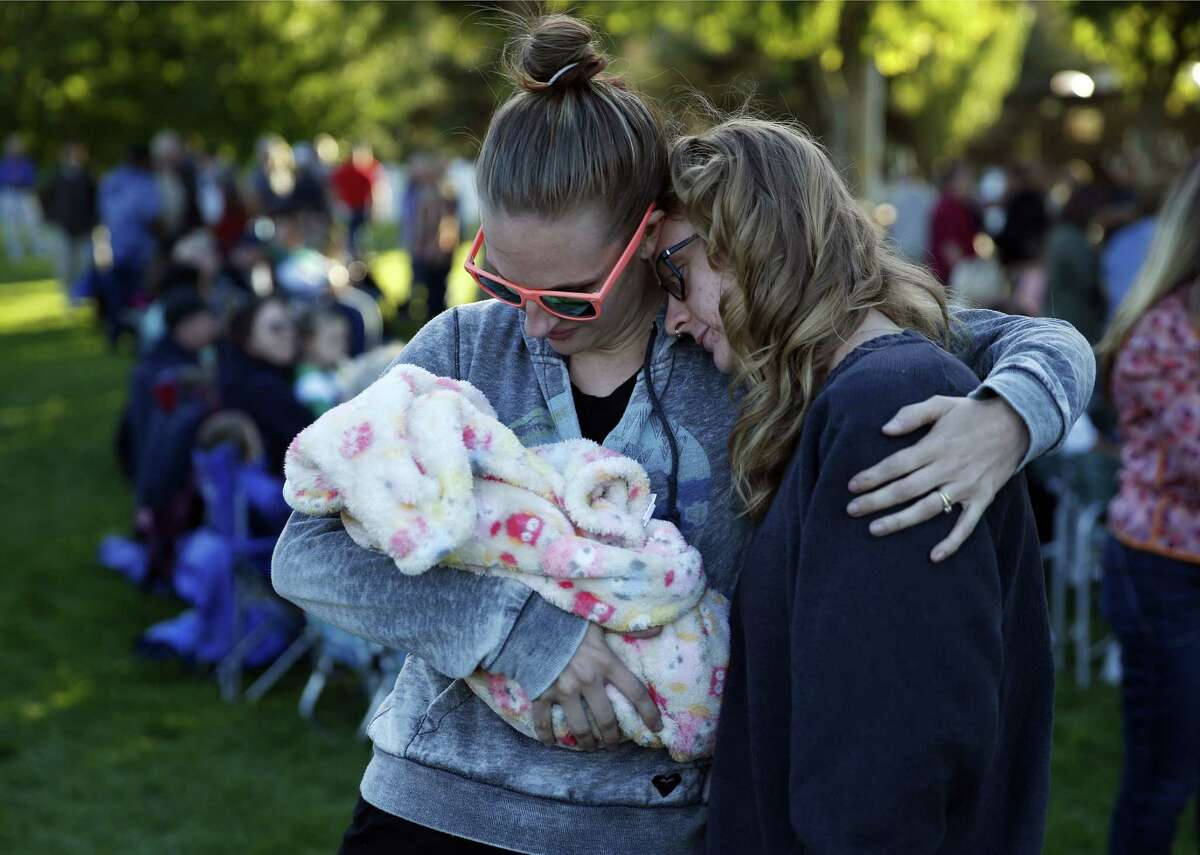 Ashley Katter, left, embraces Haley Lamphere while holding Katter's niece Ruby Abrahamson during a prayer vigil Saturday, Oct. 3, 2015, in Winston, Ore. The vigil was held in honor of the victims of the fatal shooting at Umpqua Community College on Thursday.