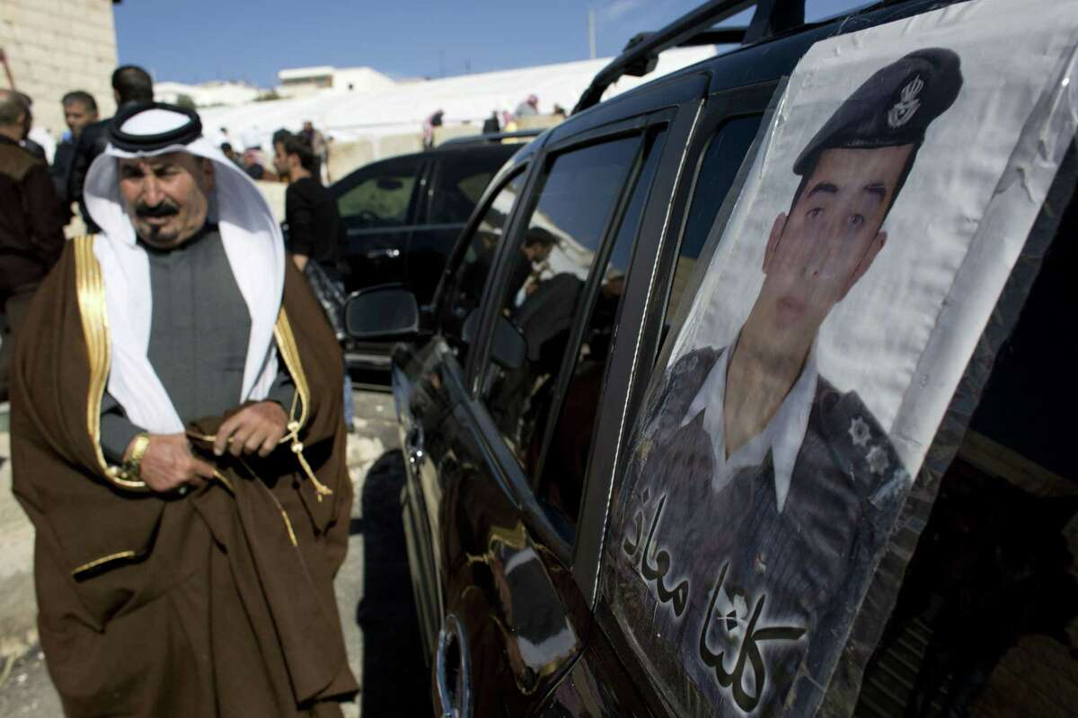 A Jordanian man walks past a poster that is pasted on a vehicle with a picture of slain Jordanian pilot, Lt. Muath al-Kaseasbeh with Arabic that reads,