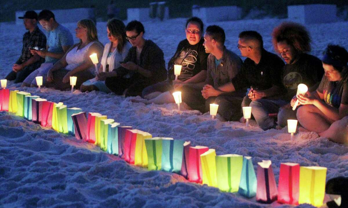 People sit near a row of lumenaria during a candle light vigil for those killed in the Orlando Night Club shooting that was held Thursday, June 16, 2016 in the Florida panhandle community of Santa Rosa Beach.