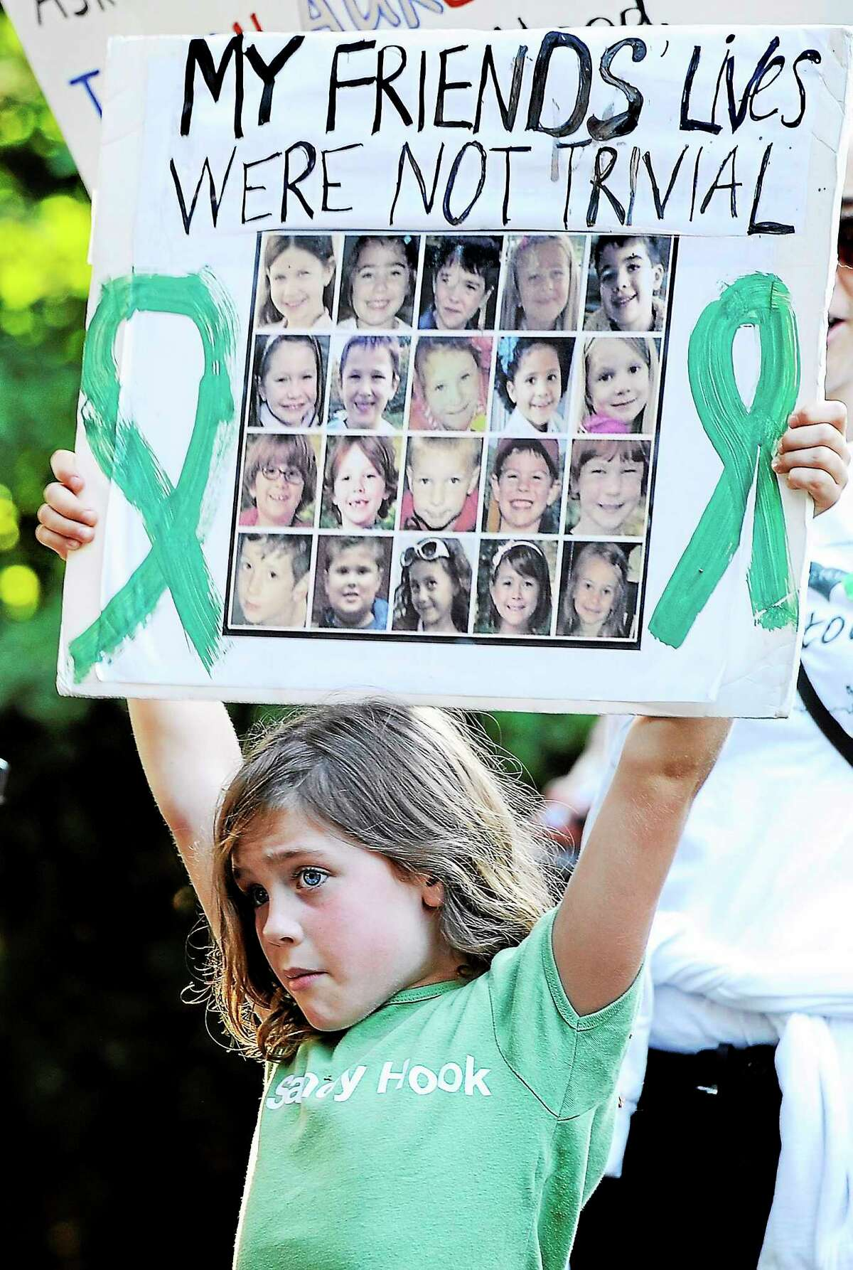 Marie Morosky of Newtown holds up a sign with images of the children killed in the Sandy Hook School shooting.