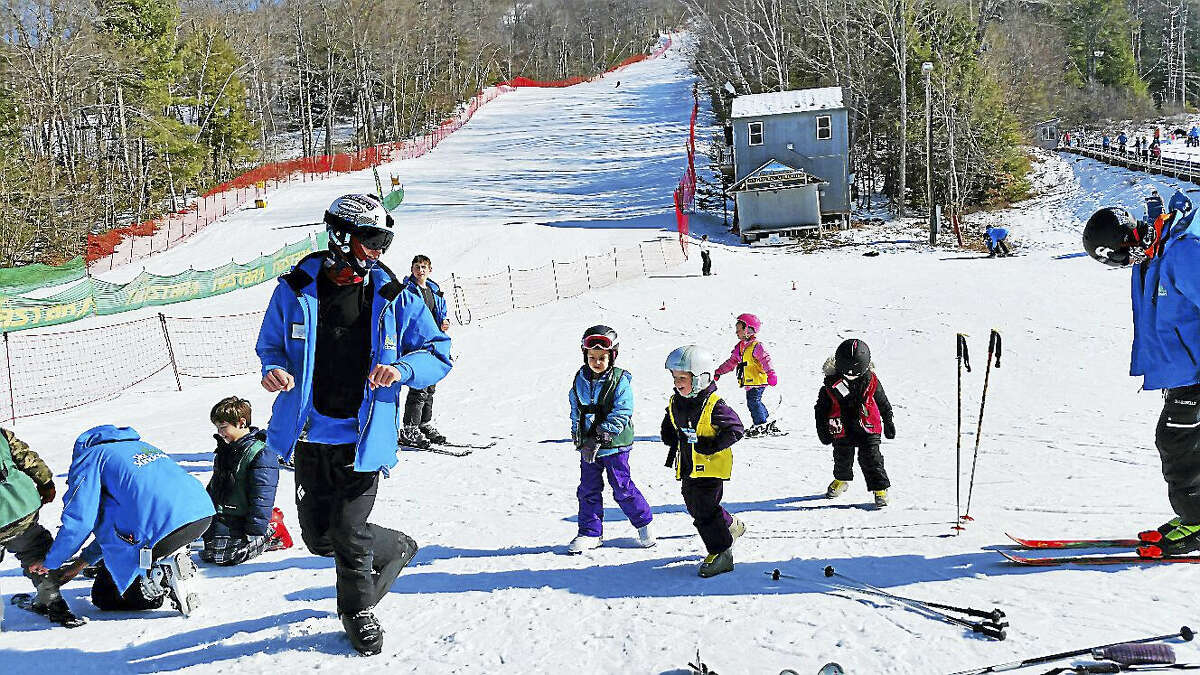 Ski instructor Andrew Hart teaches a few young students about the fundamentals of skiing.