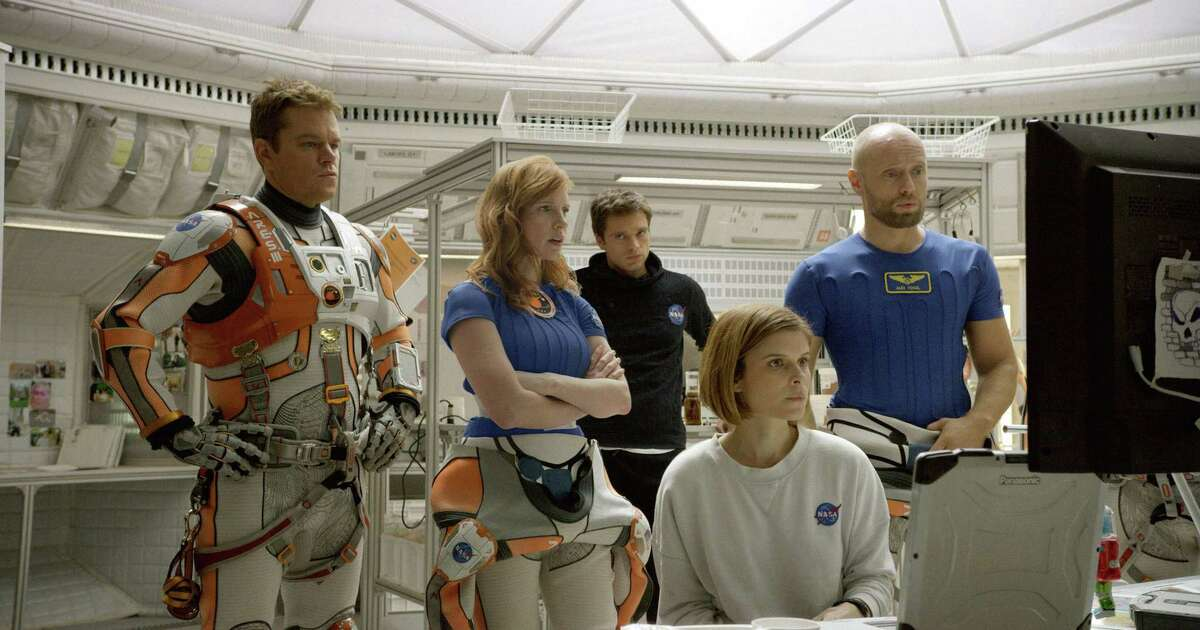 """In this photo provided by Twentieth Century Fox, Matt Damon, from left, as Astronaut Mark Watney, Jessica Chastain as Melissa Lewis, Sebastian Stan as Chris Beck, Kate Mara as Beth Johanssen, and Aksel Hennie as Alex Vogel, appear in a scene in the film, """"The Martian."""""""