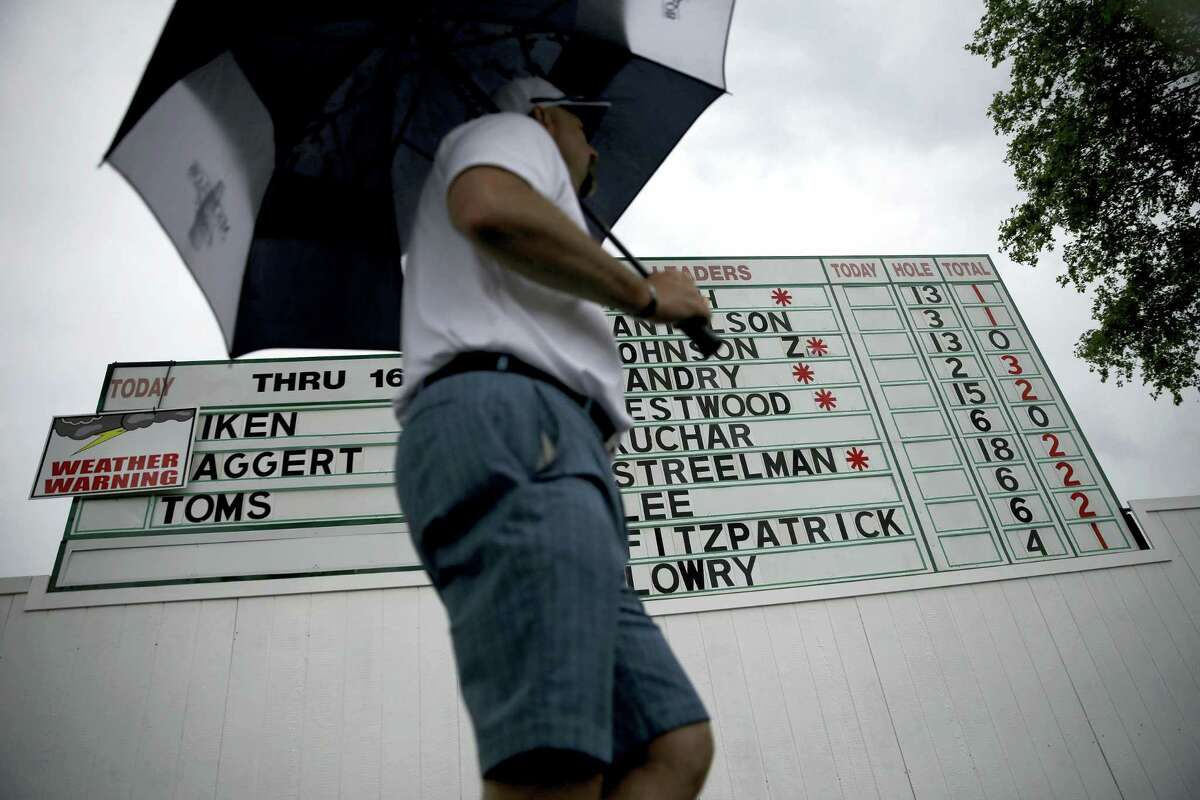 A fan with an umbrella walks past the leaderboard during a rain delay during the first round of the U.S. Open on Thursday.