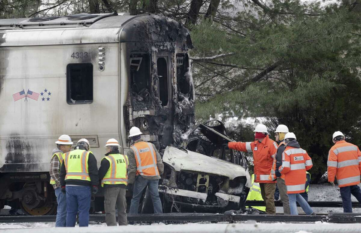 An investigator points to an SUV that was crushed and burned at the front of a Metro-North Railroad train, Wednesday, Feb. 4, 2015, in Valhalla, N.Y. The commuter train slammed into the SUV stuck on the tracks Tuesday evening, killing the driver and at least five train passengers, authorities said. (AP Photo/Mark Lennihan)