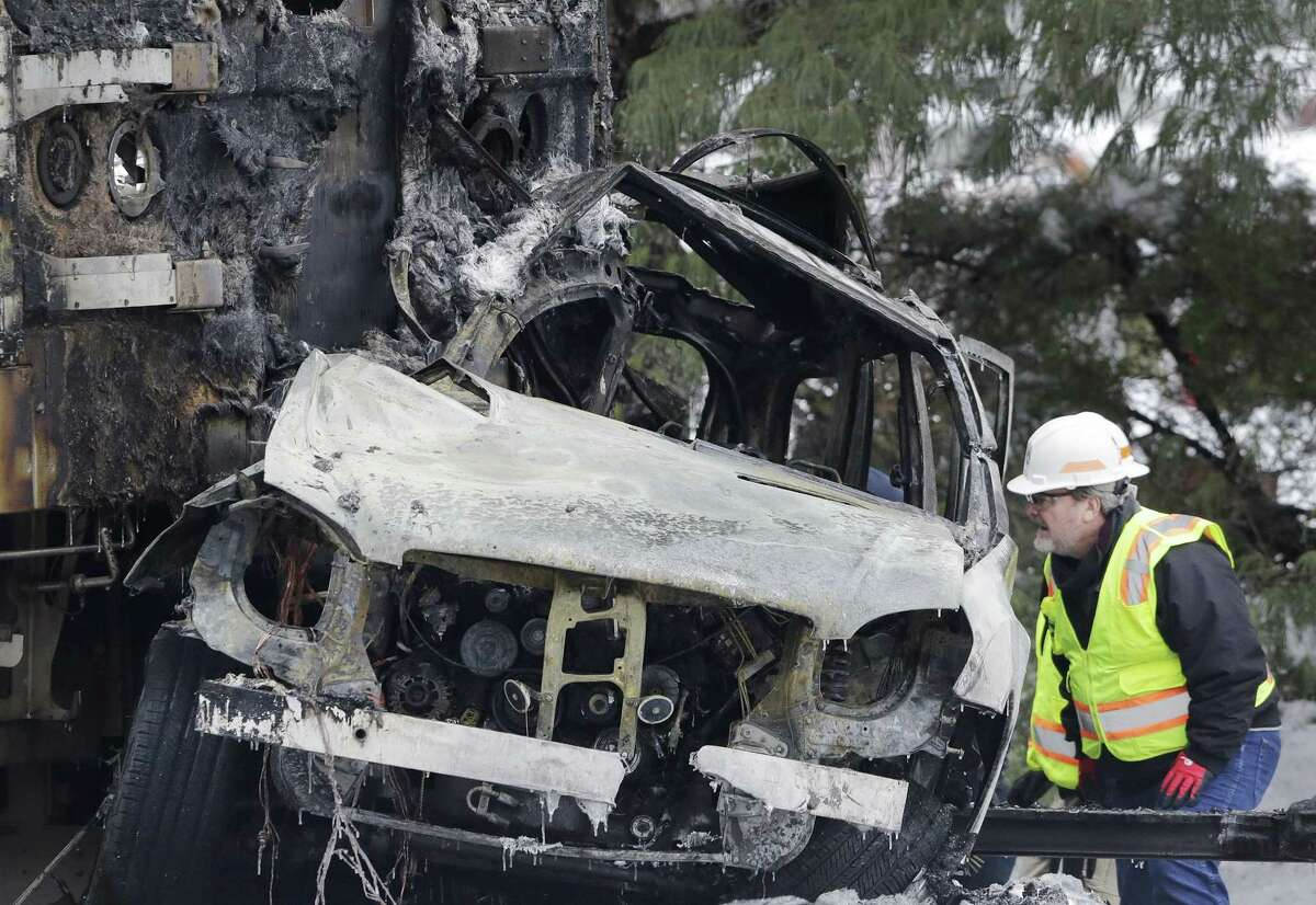 An official looks at a SUV that was crushed and burned at the front of a Metro-North Railroad train Wednesday, Feb. 4, 2015, in Valhalla, N.Y. Five train passengers and the SUVís driver were killed in Tuesday eveningís crash in Valhalla, about 20 miles north of New York City. Authorities said the impact was so forceful the electrified third rail came up and pierced the train. (AP Photo/Mark Lennihan)