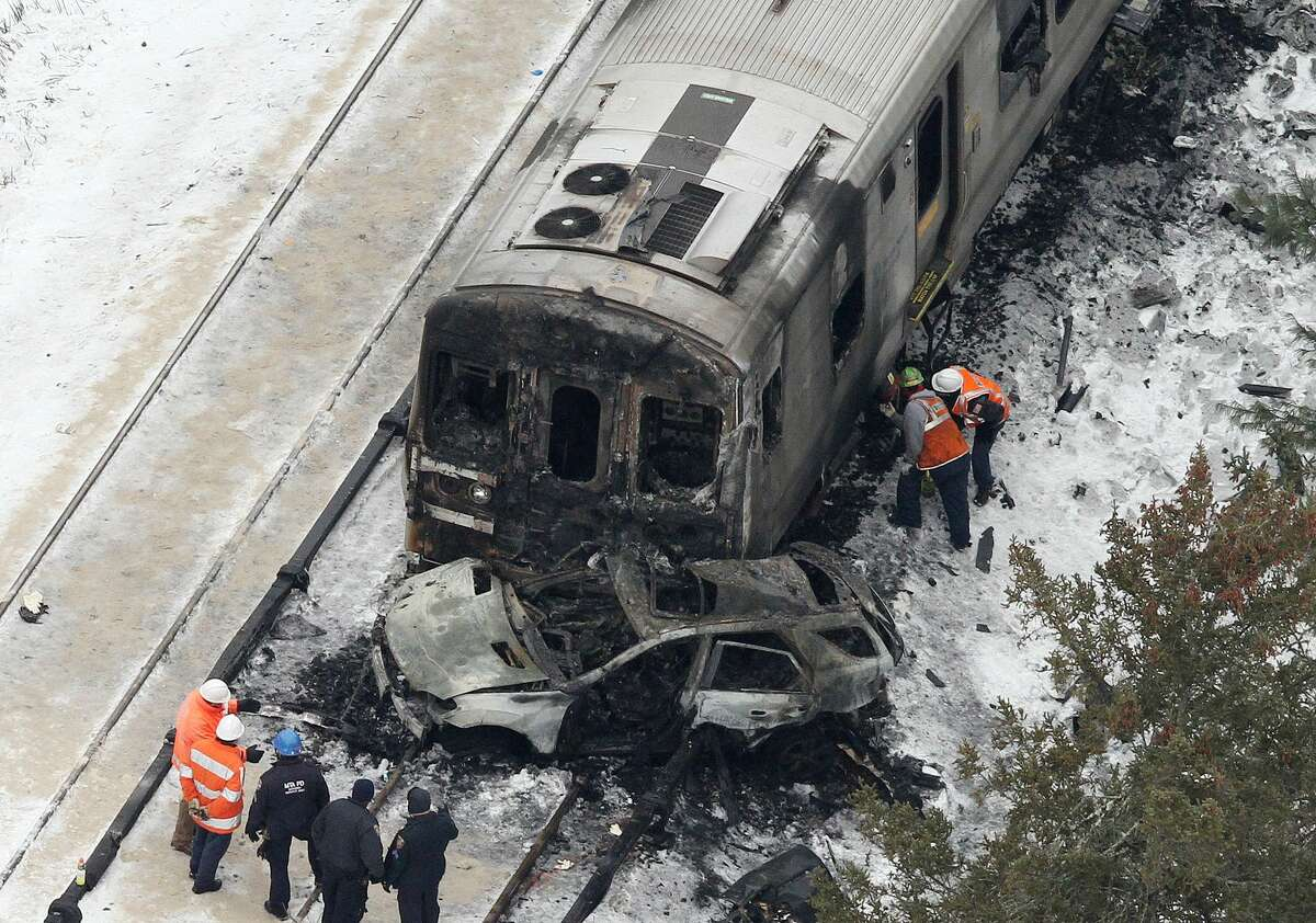 The burned out shell of an SUV, rests against a charred Metro-North Railroad commuter train as personnel from various agencies work the scene of a deadly accident in Valhalla, N.Y., Wednesday, Feb. 4, 2015. (Frank Becerra Jr. — The Journal-News)