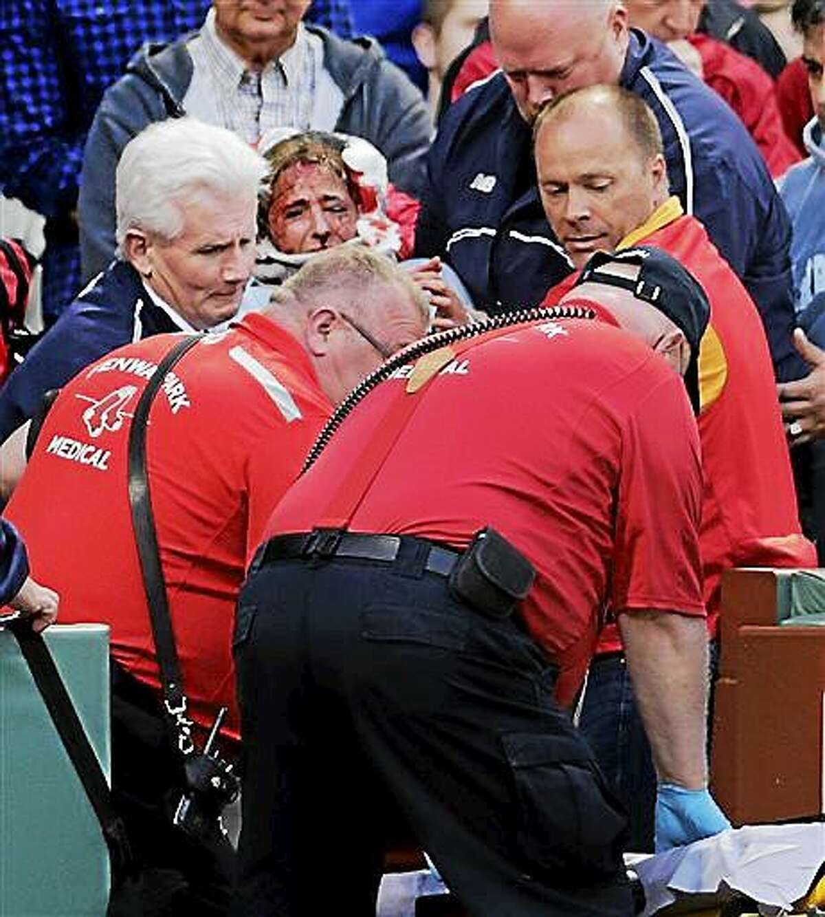 A fan, who was accidentally hit in the head with a broken bat by Oakland Athletics' Brett Lawrie, is helped from the stands during a baseball game against the Boston Red Sox at Fenway Park in Boston, Friday, June 5, 2015. The game was stopped while they wheeled her down the first base line. (AP Photo/Charles Krupa)