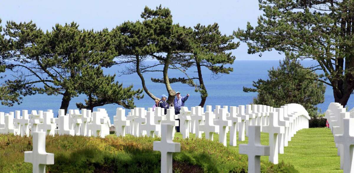 Visitors walk among graves at the Colleville American military cemetery, in Colleville sur Mer, western France, Saturday June 6, 2015, on the 71th anniversary of the D-Day landing. D-Day marked the start of a Europe invasion, as many thousands of Allied troops began landing on the beaches of Normandy in northern France in 1944 at the start of a major offensive against the Nazi German forces, an offensive which cost the lives of many thousands. (AP Photo/Remy de la Mauviniere)
