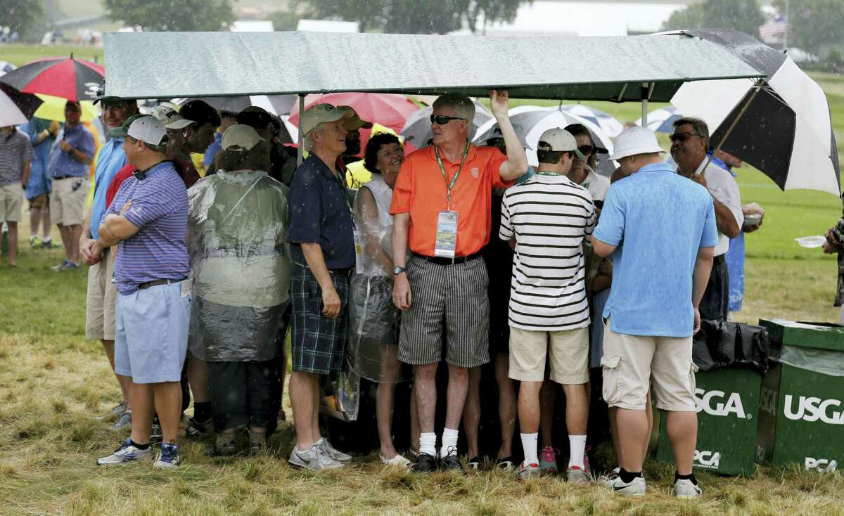 Fans take shelter from the rain after play was suspended during the first round of the U.S. Open golf championship at Oakmont Country Club on June 16, 2016 in Oakmont, Pa.