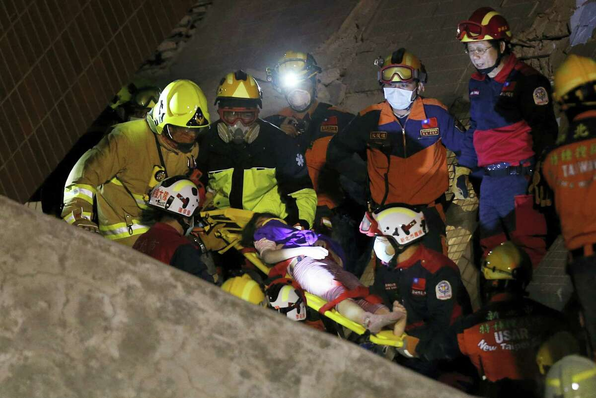 A female is rescued from a collapsed building complex after an early morning earthquake in Tainan, Taiwan, Saturday, Feb. 6, 2016. A 6.4-magnitude earthquake struck southern Taiwan early Saturday, toppling at least one high-rise residential building and trapping people inside.